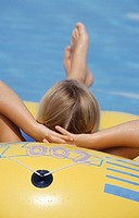 Young woman relaxing on inflatable in pool, rear view