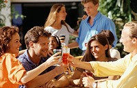 Four people raising toast at restaurant table, outdoors