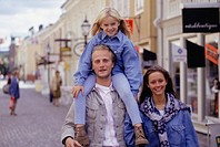 Family walking on street, daughter (6-7) on father´s shoulders