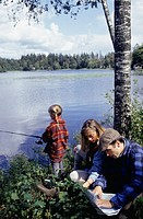 Parents studying map, girl (8-9) fishing by lake shore