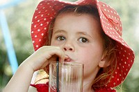 3 year old girl in a big floppy red hat, drinking through a straw