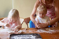 A mother baking with 2 young girls