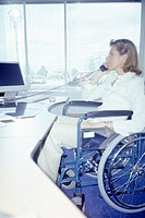 Woman in wheelchair talking on phone at desk, side view