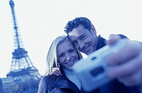 Young couple posing for photo in front of Eiffel Tower, close-up