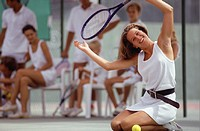Young woman kneeling on tennis court celebrating victory