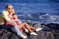 Young couple sitting on rocky beach, embracing