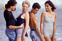 Two couples standing on beach, three quarter length