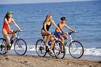 Mother with daughter (16-17) and son (12-13) riding bikes on beach