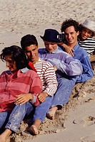 Group of friends sitting in row on sandy beach