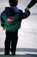 Boy (4-5) walking on street, holding hand of parent, rear view