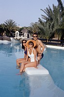 Two women and man in sunglasses sitting in pool, portrait