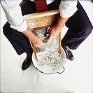 Businessman washing money on washboard, elevated view