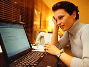 Woman working with laptop, (Close-up)