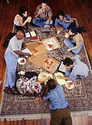Group of businesspeople working and eating pizza on rug, elevated view