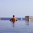 Female swimmer on edge of pool by sea