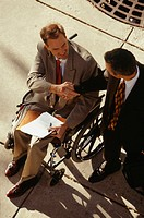 Businessmen, one in wheelchair, shaking hands, elevated view