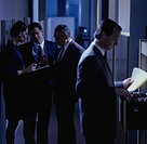 Businesspeople standing in darkened office corridor