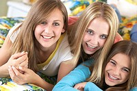 Three teenage girls (12-14) lying on bed, smiling, portrait, close-up