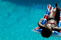 Woman on pool raft in swimming pool
