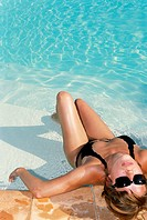 Woman leaning against pool side