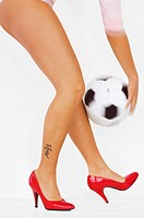 Woman with red high heels holding soccer ball