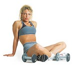 a curly haired blond female weightlifter is wearing gray and sitting cross-legged on the floor next to her dumb bells