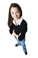 an asian female teen in jeans and a black sweater folds her arms and smiles up at the camera
