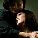 studio portrait of an asian mother as she smiles holding her teenage daughter
