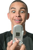 an african american teenage male acts surprised as he gets info of his cell phone