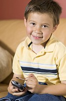 lifestyle shot of a male child as he sits on a couch and with a pda and smiles