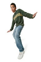 an african american teenage boy in jeans and a green sweater throws out his arms and strikes a fun surfing pose