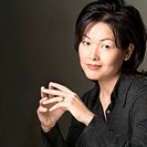 portrait of an attractive asian woman in a black shirt as she claps her hands together and smiles