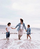 a mother holds her two son´s hands on the seashore