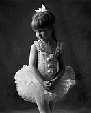 A young caucasian ballerina poses quietly