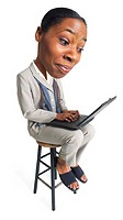 a young african american business woman sits with a computer on her lap and types away