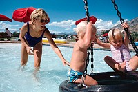 young mother pushes tire swing in a public pool with her two blonde toddlers