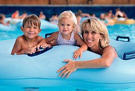 blonde mother and two young children rest on a blue pool raft