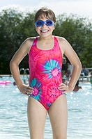 lifestyle portrait of a female child in a pink swimsuit and goggles as she stands in a pool and smiles