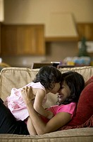 lifestyle shot of a mother as she lays on the couch and plays with her toddler daughter