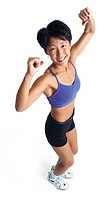 an adult asian female in a blue sports bra and black shorts stands exercising and lifting her arms above her head