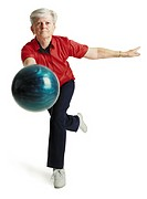 an elderly caucasian woman with white hair runs toward the camera wearing a red shirt and about to throw her blue bowling ball