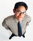 a handsome young latino man in glasses wearing a gray dress shirt and tie smiles looking up into the camera