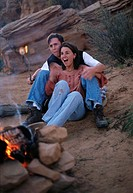 a young couple are sitting together by a campfire attemping to put out a marshmallow that has caught fire with the desert in the backgorund