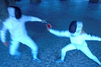Two fencers in action fencing