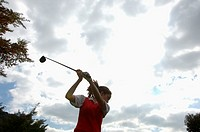 A woman in action of the backswing with a golf club
