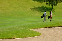 Couple with their golf bags walking near a bunker