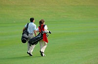 Rear view of a couple walking on the fairway as they carry their golf bags