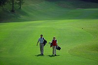 Couple walking on the fairway carrying their golf bags