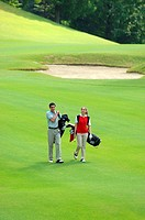 Side view of a couple walking on the fairway as they carry their golf bags