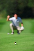 Butterfly on golf ball in foreground as man lines up a putt